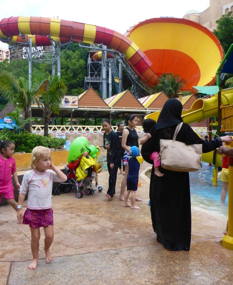 Mathilda passes one of many women in full burqa at Sunway Lagoon's waterpark.